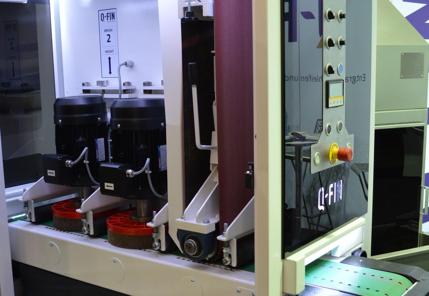 Blick in die F200 XL – die Maschine arbeitet mit einem Schleifband und zwei nachgeordneten Topfbürsten. Die Teile können in zwei Spuren aufgelegt werden und werden über Vakuum durch die Löcher im Transportband gehalten.