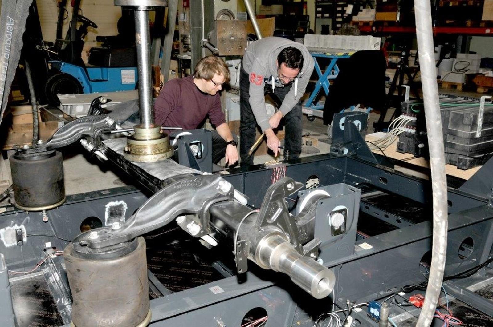 Mehr Sicherheit für Nutzfahrzeuge: Materialwissenschaftler Dr.-Ing. Andree Irretier (r.) und Rolf Klemm führen Körperschallmessungen am Achsbereich eines LKW-Trailers durch.
