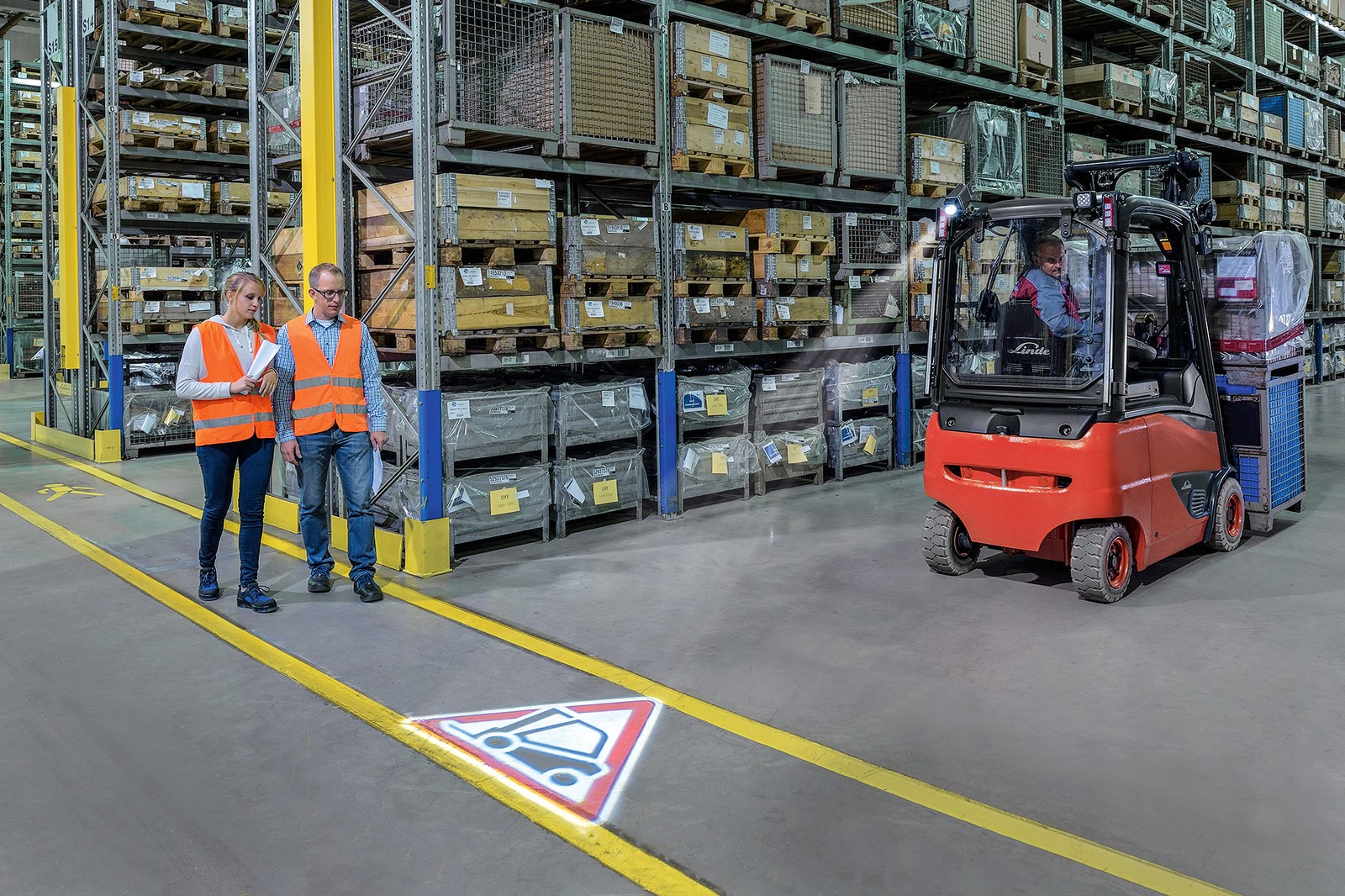 Der Linde Truck Spot ist eine Weiterentwicklung des Blue Spots. Das optische Warnsystem projiziert ein rotes Dreieck hinter sich auf den Boden und weist andere Personen auf einen nahenden Stapler hin.
