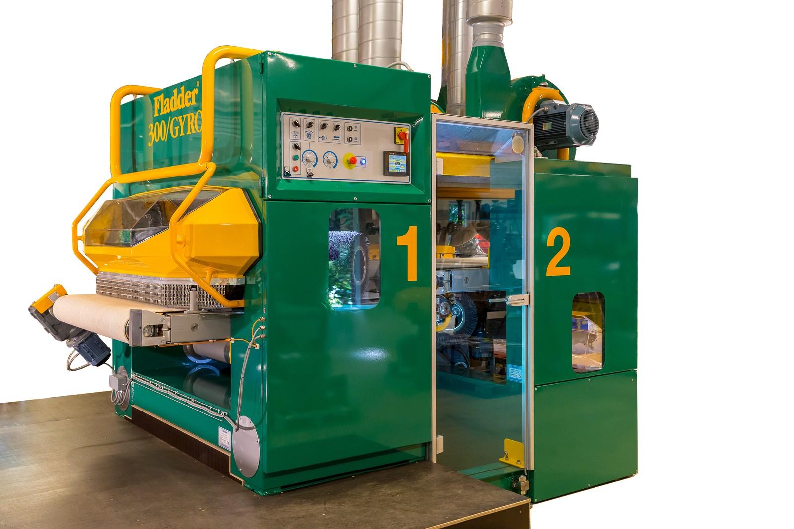 Eine normale Maschine (1) zum Entgraten der Oberseite und eine Maschine (2) zum Entgraten der Unterseite.