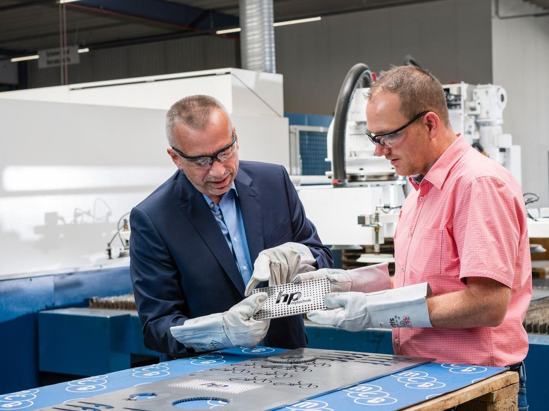 Für eine effiziente Fertigung ist die Materialauswahl wichtig, das gilt vor allem bei Lasergüten. Thomas Bauer, MCB Deutschland (li) und Markus Kahlert, HP-Polytechnik oHG, prüfen Laserteile.