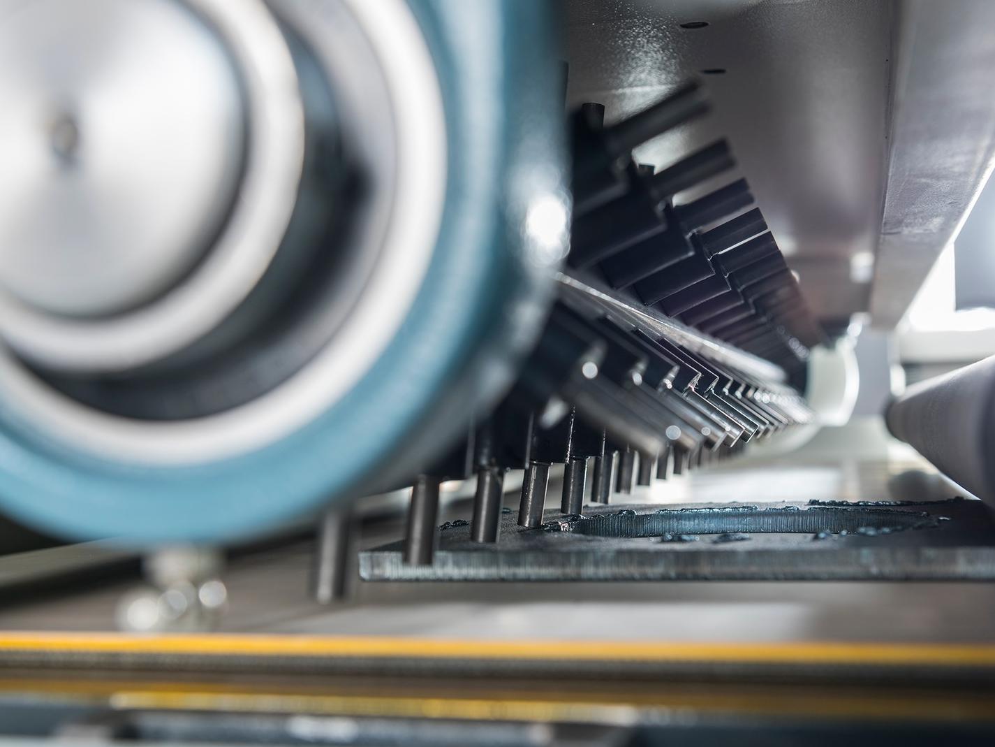 Die 42 Series HWRB Rotationsbürstenmaschine wird mit dem neuen Hammerhead zur Entfernung schwerer Schlacke gezeigt.